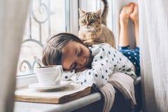 Niño que se relaja con un gato en un travesaño de la ventana Fotografía de archivo libre de regalías