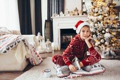 Niño que se relaja por el árbol de navidad en casa imagen de archivo