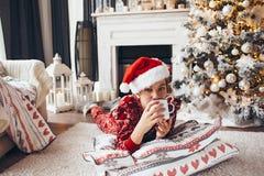 Niño que se relaja por el árbol de navidad en casa Imagenes de archivo
