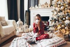 Niño que se relaja por el árbol de navidad en casa fotografía de archivo