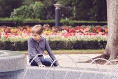 Niño que se sienta cerca de la fuente en el parque de la ciudad Fotografía de archivo libre de regalías