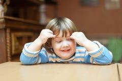 Niño que se sienta con los ojos cerrados foto de archivo