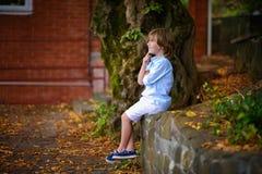 Niño que se sienta debajo de árbol grande Imagenes de archivo
