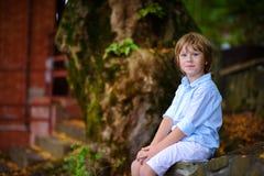 Niño que se sienta debajo de árbol grande Imagen de archivo libre de regalías