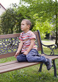 Niño que se sienta en banco Fotografía de archivo