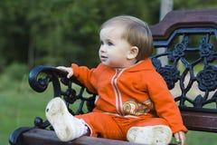 Niño que se sienta en el banco Imagenes de archivo