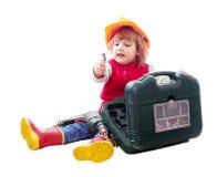 Niño que se sienta en el casco de protección con las herramientas Imagen de archivo libre de regalías