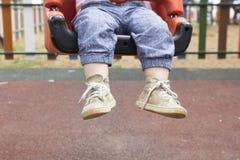 Niño que se sienta en el oscilación en parque foto de archivo libre de regalías