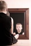 Niño que se sienta en el piso que mira fijamente en el espejo Imagen de archivo libre de regalías