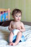 Niño que se sienta en el pote de cámara en el cuarto Fotografía de archivo libre de regalías