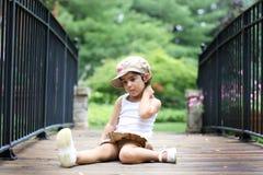 Niño que se sienta en el puente fotos de archivo libres de regalías