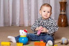 Niño que se sienta en jugar del piso Foto de archivo libre de regalías