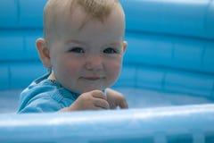Niño que se sienta en la piscina Fotografía de archivo libre de regalías