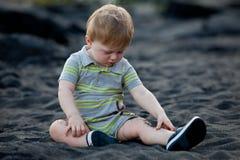 Niño que se sienta en la playa negra de la arena Imagenes de archivo