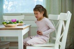 Niño que se sienta en la tabla en la cocina con dolor de estómago foto de archivo