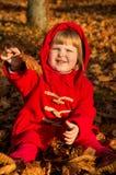 Niño que se sienta en la tierra en otoño Fotos de archivo libres de regalías