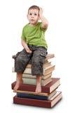 Niño que se sienta en los libros Imágenes de archivo libres de regalías