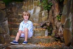 Niño que se sienta en pasos Imagen de archivo libre de regalías
