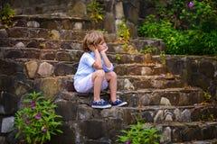 Niño que se sienta en pasos Foto de archivo