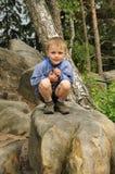 Niño que se sienta en piedra Fotografía de archivo libre de regalías