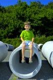 Niño que se sienta en un tubo Imagen de archivo libre de regalías