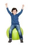 Niño que se sienta en una bola de los pilates imagenes de archivo