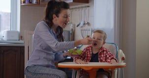 Niño que se sienta en una silla del bebé y que come la comida con la madre metrajes