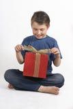 Niño que se sienta que abre un presente foto de archivo libre de regalías