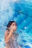Niño que se zambulle bajo el agua en piscina Imagenes de archivo