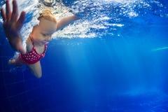 Niño que se zambulle bajo el agua en piscina Imagen de archivo