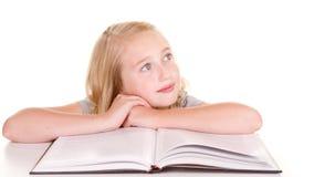 Niño que soña despierto mientras que lee Fotografía de archivo libre de regalías