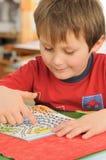 Niño que soluciona el laberinto Fotografía de archivo