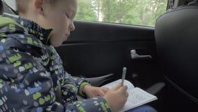 Niño que soluciona rompecabezas del ajedrez durante viaje en coche almacen de metraje de vídeo
