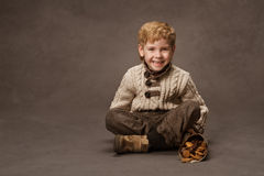 Niño que sonríe en suéter hecho punto. Moda del muchacho en estilo retro. Br Imagenes de archivo