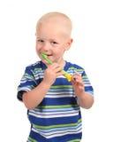 Niño que sonríe y que aplica sus dientes con brocha Fotografía de archivo libre de regalías