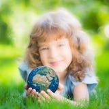 Niño que sostiene el planeta de la tierra en manos Imagen de archivo
