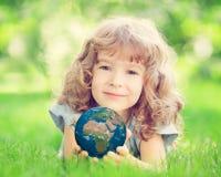 Niño que sostiene el planeta de la tierra en manos Fotografía de archivo libre de regalías