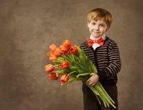 Niño que sostiene el ramo de las flores de los tulipanes Fotografía de archivo