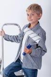 Niño que sostiene el rodillo de pintura Imagenes de archivo