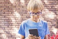 Niño que sostiene el teléfono móvil al aire libre El muchacho con los vidrios mira la pantalla del smartphone, uso del uso, juego Foto de archivo libre de regalías