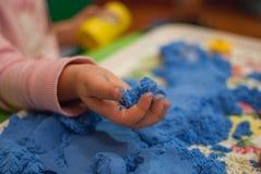 Niño que sostiene la arena azul Imágenes de archivo libres de regalías