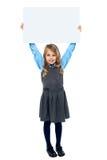 Niño que sostiene la cartelera en blanco sobre su cabeza fotografía de archivo