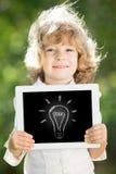 Niño que sostiene la PC de la tablilla Imágenes de archivo libres de regalías