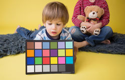 Niño que sostiene la tarjeta del inspector del color de la fotografía Imagen de archivo