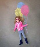 Niño que sostiene los globos coloridos de la tiza en la acera Imágenes de archivo libres de regalías