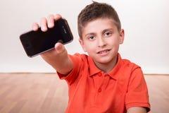 Niño que sostiene smartphone Imagen de archivo libre de regalías