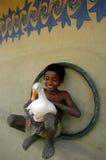 Niño que sostiene un pato Imagenes de archivo