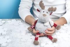 Niño que sostiene un reno de la Navidad del juguete imagen de archivo
