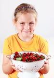 Niño que sostiene un tazón de fuente de cerezas frescas Fotos de archivo