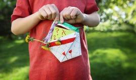 Niño que sostiene una cesta hecha en casa de flores Foto de archivo libre de regalías